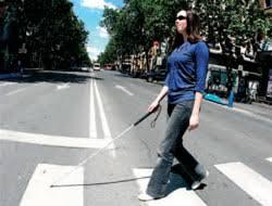 Mujer invidente haciendo travesía en un paso de cebra